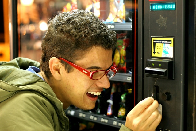 Young adult wearing glasses putting coin in vending machine