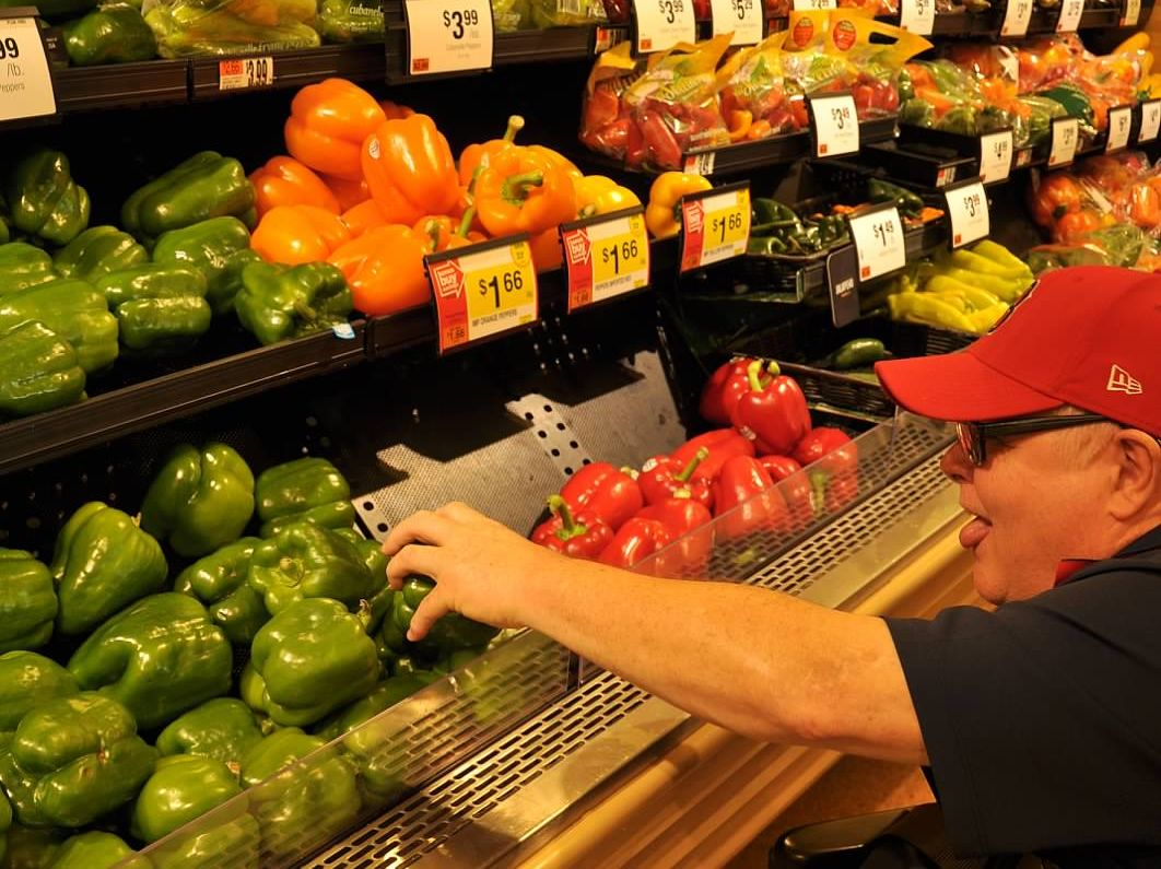 man wearing glasses and baseball cap reaching for pepper in grocery store